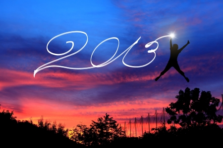 Young man jumping and drawing 2013 before sunrise sky Stock Photo