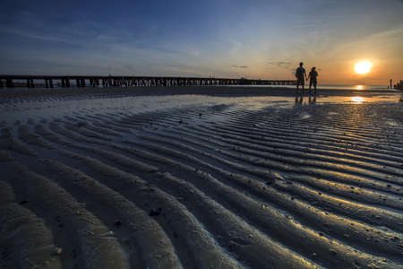 Young couple standing on the beach and watching the sunrise photo
