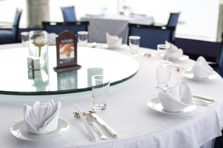 Glasses and plates on table in restaurant - food background photo