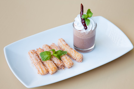 gressins: Gressins dans une tasse blanche et sauce brune sur assiette blanche