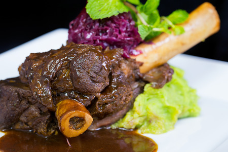 jus: Lamb shank braised in an onion jus on white plate Stock Photo