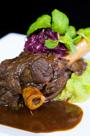 Lamb shank braised in an onion jus on white plate Stock Photo