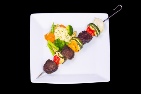 grilled beef shishkabobs on table close up photo
