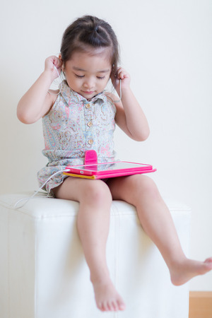 Little Girl playing Tablet Computer at her house Stock Photo