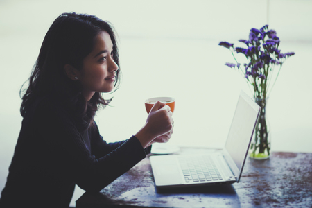 Asian  woman working with her laptop and coffee on desk, Vintage color