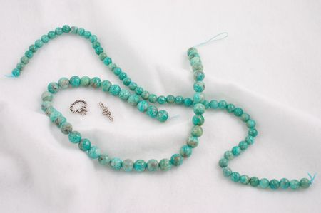 amazonite: Amazonite beads with silver clasps on fluffy cotton-like fabric