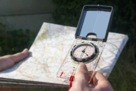 hand held: Compass hand held over blurred map as if taking a bearing