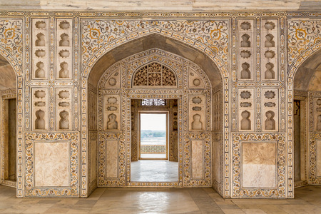 Decorated marble wall frames gate and door at Agra Fort Palace in India  Alcoves and yellow red green in-lay marble work of royal chambers, Taj Mahal in the far distance