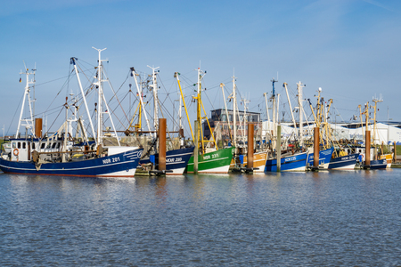 Norddeich, Germany - March 26, 2016: Fishing Boats in a Harbour and a Blue Sky Editorial