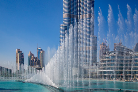 The Dubai Fountain, the world largest choreographed fountain on Burj Khalifa Lake, performs to the beat of the selected music at sunset. On background, skyscrapers of Old Town Island near Dubai Mall. Фото со стока - 71613799