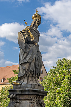 Statue of St. Cunigunde as Holy Roman Empress stands over the Regnitz river in Bamberg, Bavaria, Germany. Built 1750 from Johann Peter Benkert Stock Photo