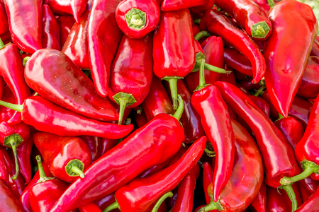 a pile of long red chillies at the vegetables market