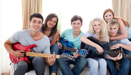 Group of teenagers playing guitar at home photo