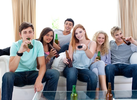 Friends drinking beer at home and watching tv Stock Photo - 10074067