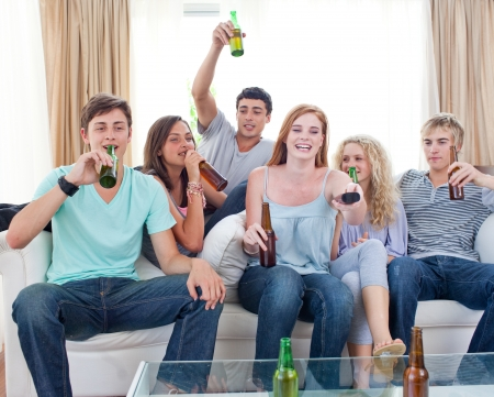 Friends drinking beer at home and watching tv photo