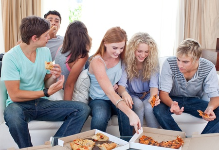 Adolescents eating pizza at home photo