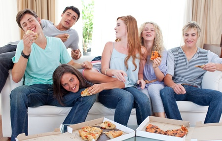 Teenagers eating pizza at home photo