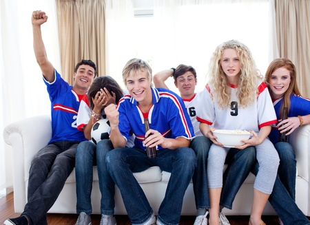 Teenagers watching a football match in the living-room photo