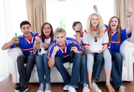 Teenagers watching a football match in the living-room Stock Photo - 10075580