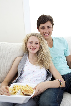 Teen couple eating burgers and fries photo