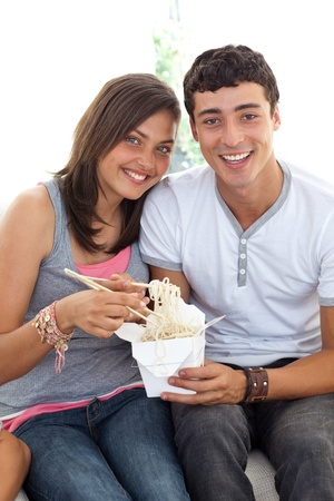 Smiling couple of teenagers eating pasta photo