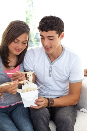 Couple of teenagers eating pasta photo