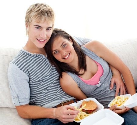Teen couple eating burgers and fries at home photo
