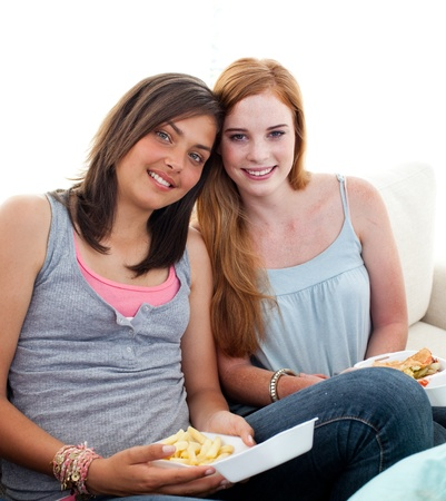 Young girls eating burgers and fries photo