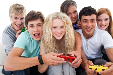 Portrait of teenagers playing video games in the living-room photo