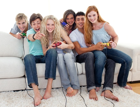 Friends playing video games in the living-room photo