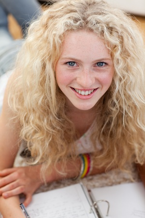 Portrait of a smiling teenager studying on the floor Stock Photo - 10075581