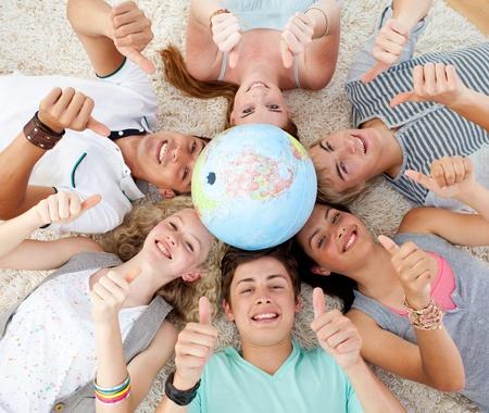 terrestre: Adolescenti sul pavimento con un globo terrestre al centro e con i pollici fino