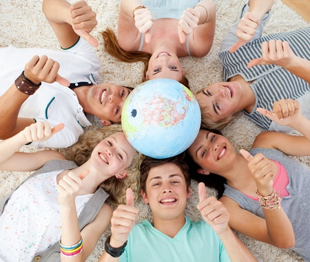terrestrial globe: Teenagers on the floor with a terrestrial globe in the center and with thumbs up