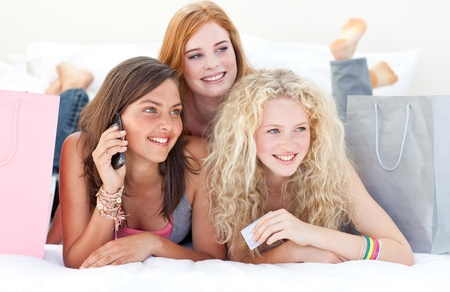 Happy teen girls after shopping clothes talking on phone photo