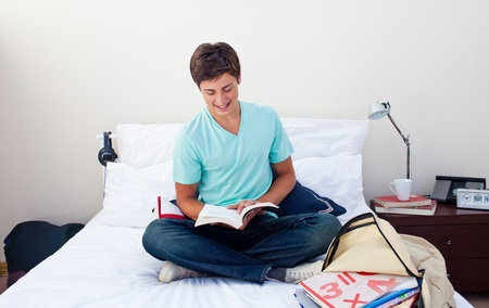 Smiling teenager reading a book in his bedroom photo
