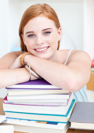 Smiling teeenager studying lots of books photo