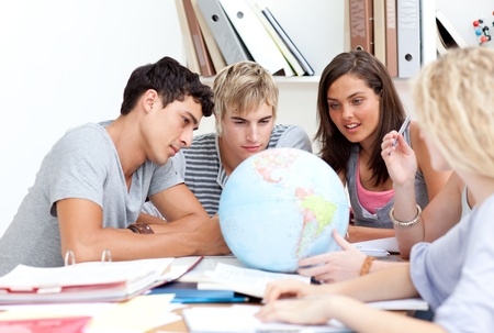 terrestrial: Teenagers in a library working with a terrestrial globe Stock Photo