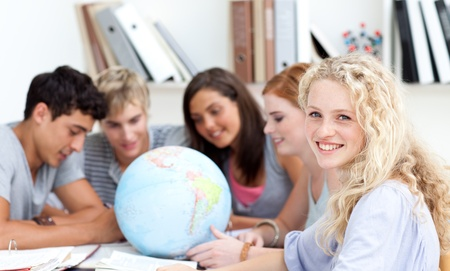 Teenagers in a library working with a terrestrial globe photo