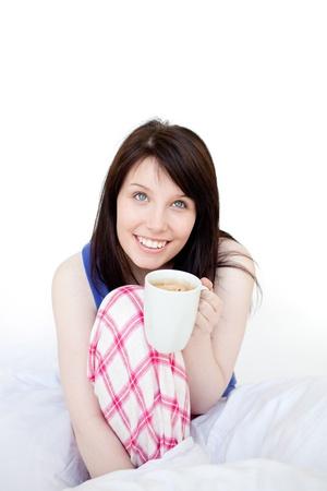 mirthful: Mirthful woman drinking coffee sitting on bed