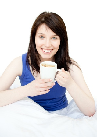 Happy woman drinking a coffee sitting on her bed  photo