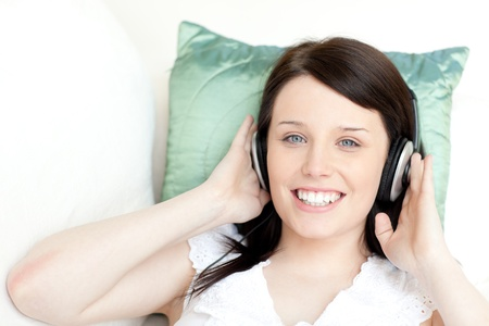 Smiling young woman listening music with headphones  photo