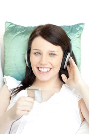 Happy young woman listening music with headphones photo