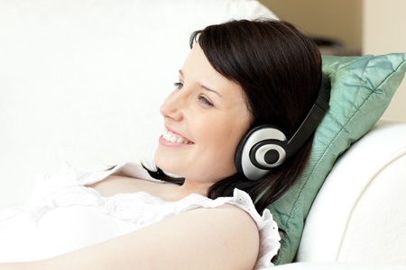 Charming young woman listening music with headphones photo