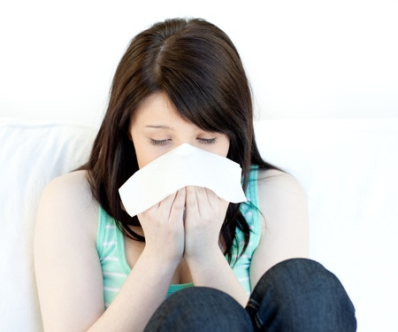 sneeze: Sick teen girl blowing sitting on a sofa