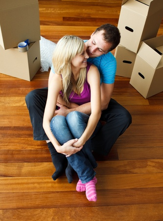 Happy young couple sitting on floor. Moving house photo