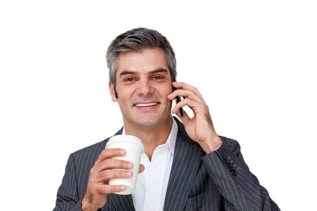 Happy businessman talking on phone and drinking coffee photo