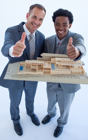 Architects holding a model house with thumbs up photo
