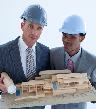 Close-up of architects holding a model house in office photo
