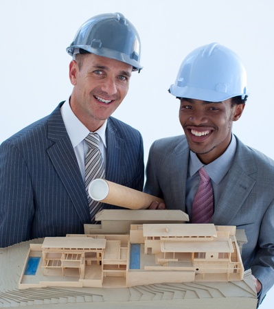 Smiling engineers with hard hats holding a model house photo