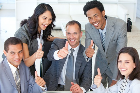 Happy businessteam with thumbs up in office Stock Photo - 10075740